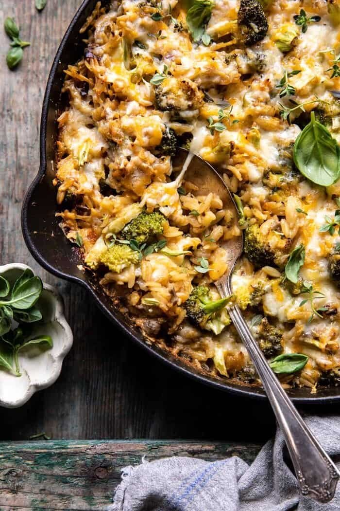 overhead close up photo of One Skillet Cheesy Broccoli Cheddar Orzo Bake with spoon in skillet