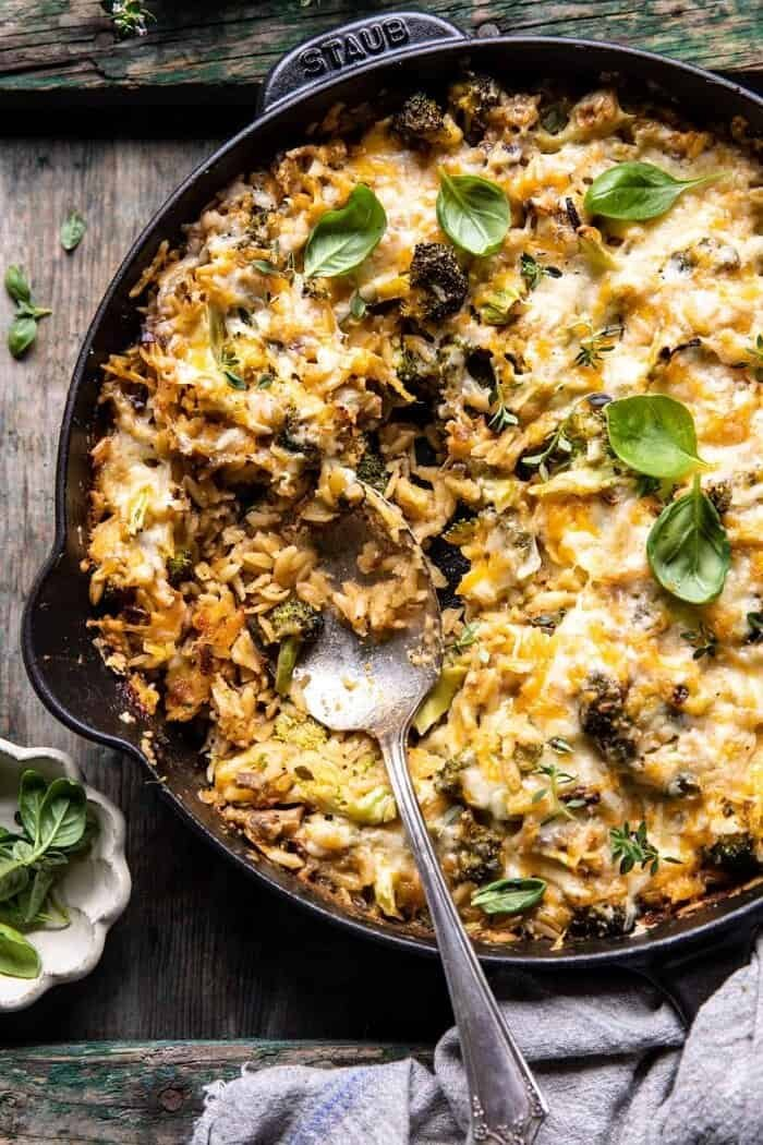 overhead photo of One Skillet Cheesy Broccoli Cheddar Orzo Bake with spoon in skillet