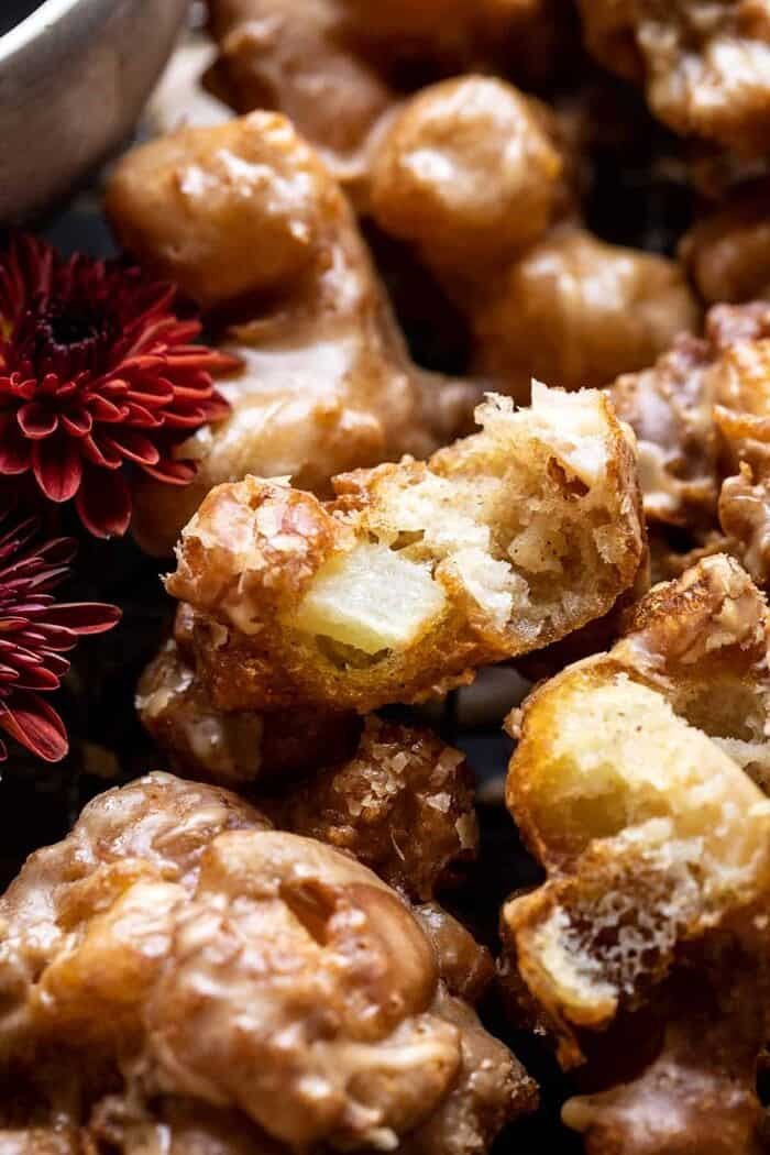 side angled photo of Cinnamon Spiced Apple Fritters with Vanilla Coffee Glaze broken in half