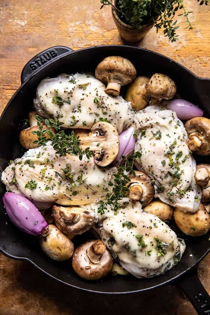prep photo of Herbed Ricotta Stuffed Chicken and mushrooms in pan before roasting