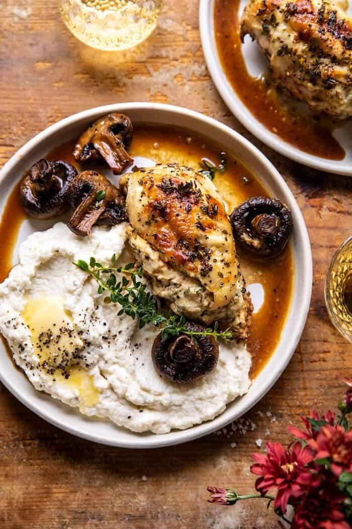 overhead photo of Herbed Ricotta Stuffed Chicken In White Wine Pan Sauce on a plate with mashed cauliflower
