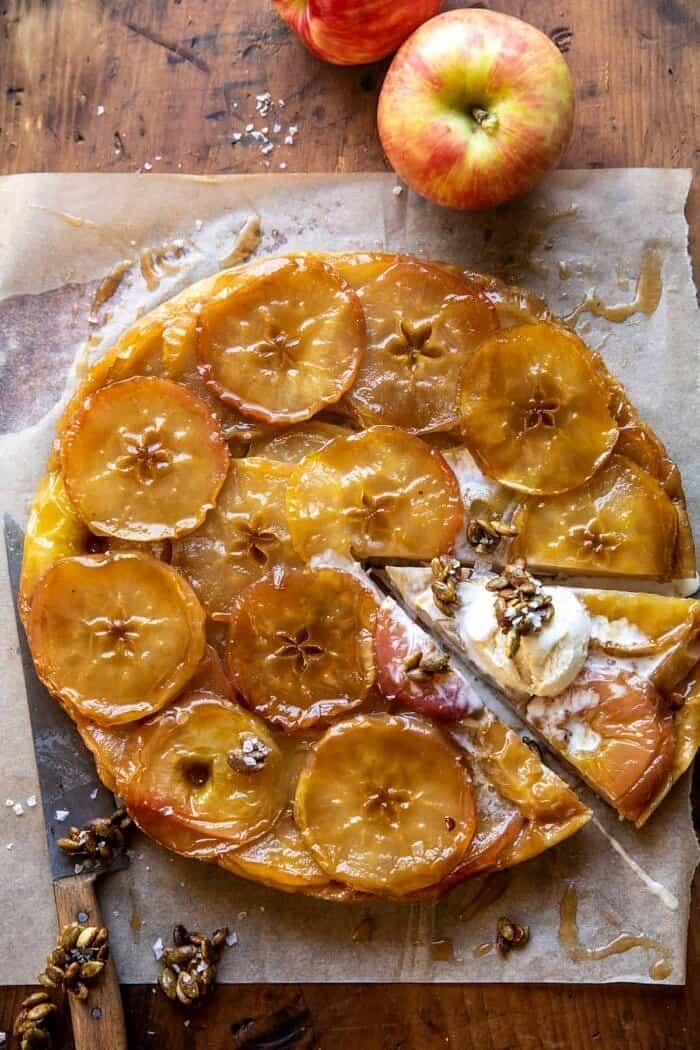 overhead photo of Salted Maple Apple Tarte Tatin with Cinnamon Pumpkin Seeds with 1 slice cut and ice cream