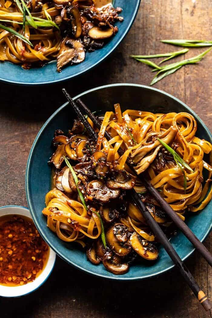 overhead photo of 30 Minute Saucy Ginger Sesame Noodles with Caramelized Mushrooms with chopsticks in bowl
