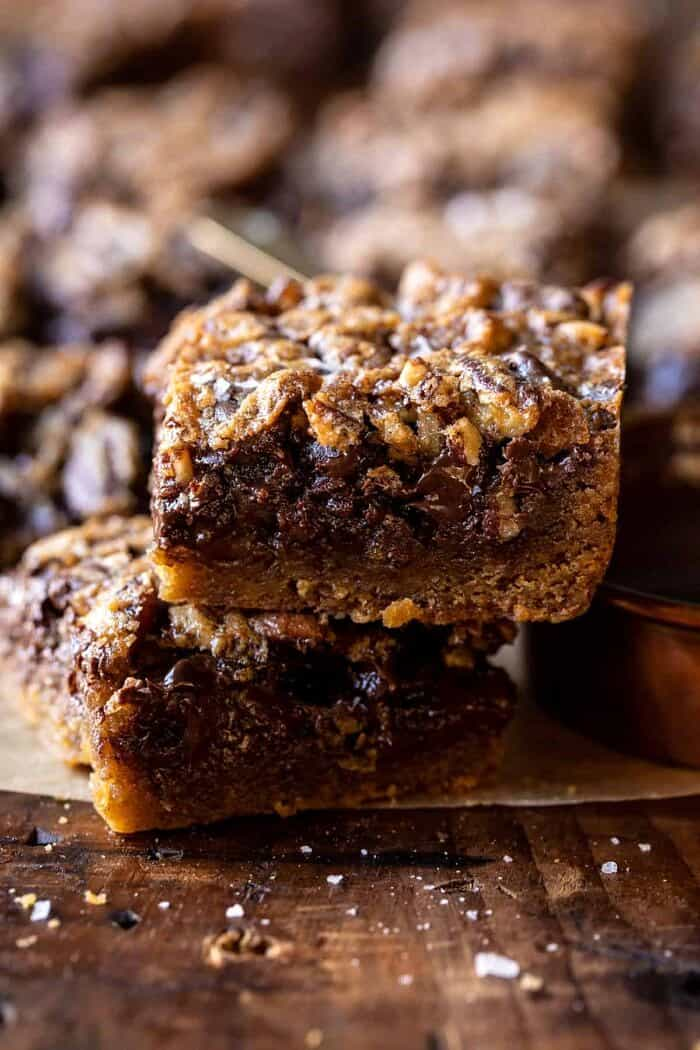 side angled photo of Brown Sugar Maple Chocolate Pecan Pie Bars with 2 bars stacked on top of each other