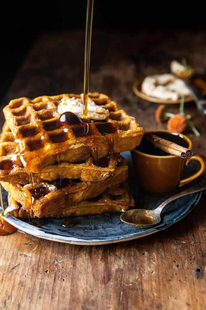 side angled action photo of Cider Pumpkin Waffles with Salted Maple Butter (the maple is being poured on the waffles)