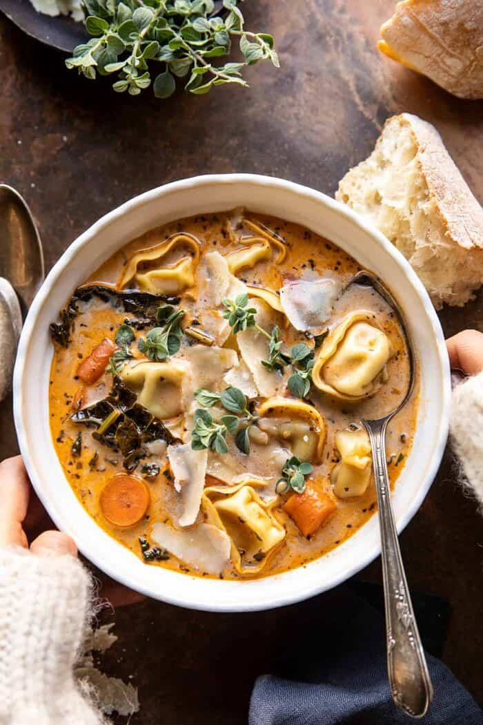 overhead photo of Healthier Slow Cooker Creamy Tortellini Vegetable Soup with 2 hands on bowl