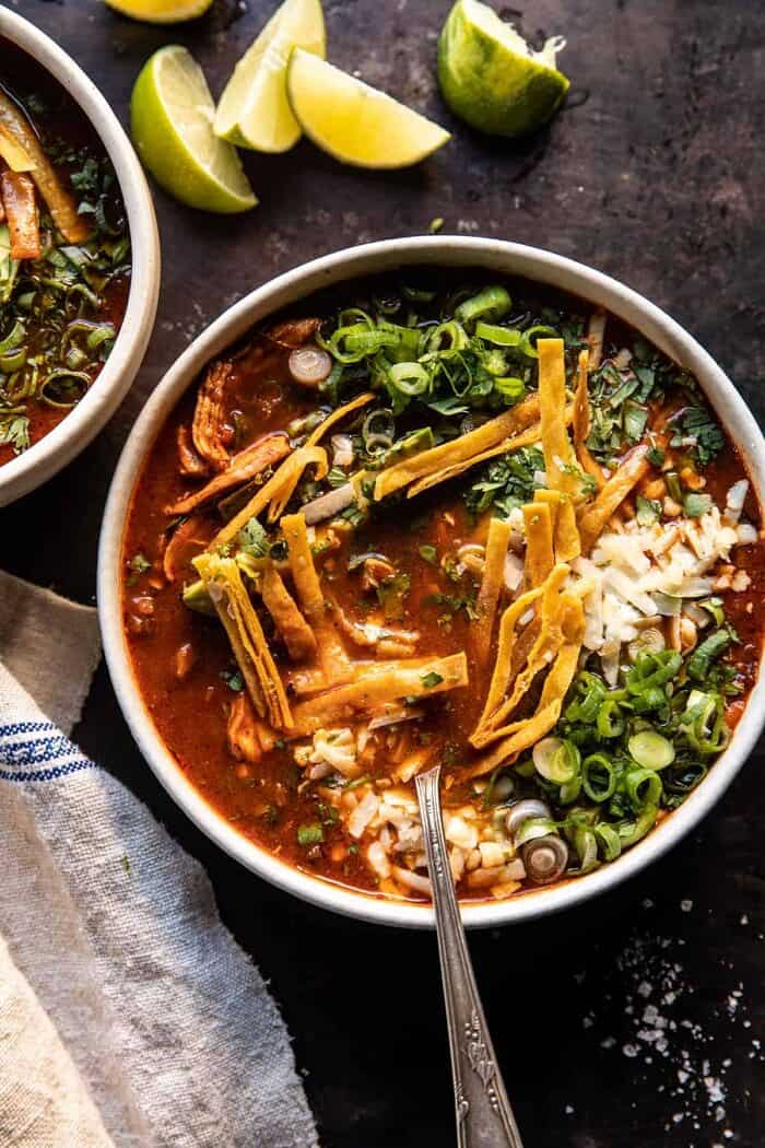 overhead photo of Slow Cooker Chipotle Chicken Tortilla Soup with Salty Lime Chips with spoon in bowl